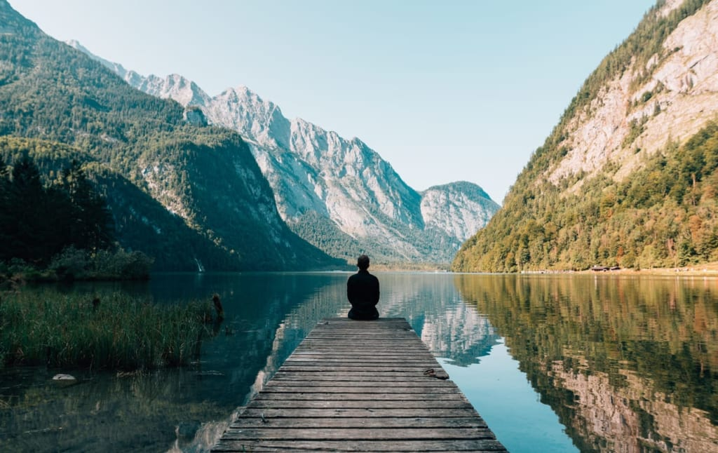 荘厳な景色の中瞑想する男性