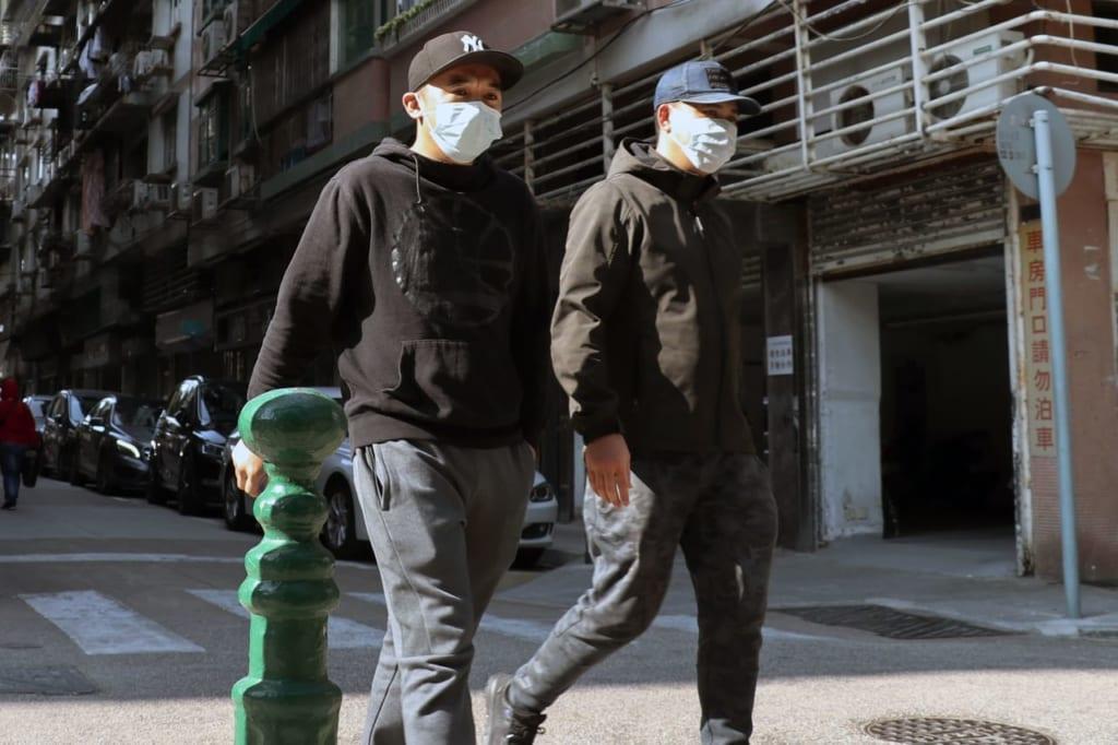 マスクをつけて歩く男性たち