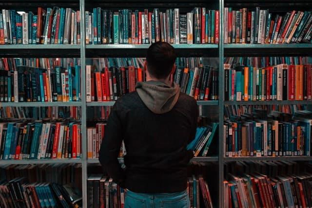図書室で本を選ぶ男性
